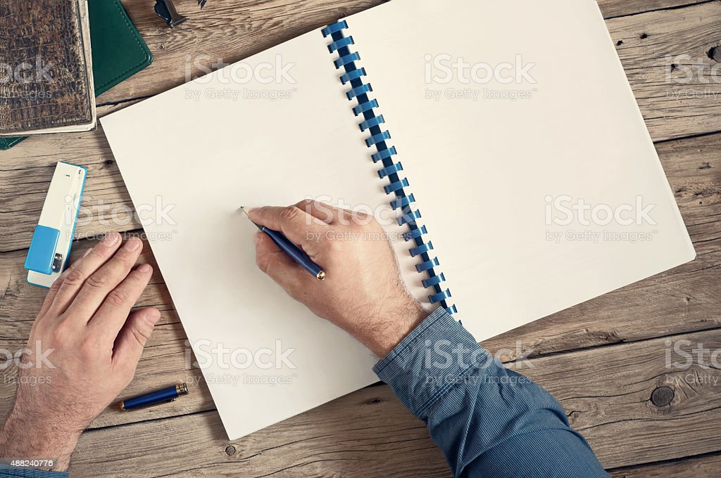 The men writes in an open notebook with blank pages stock photo