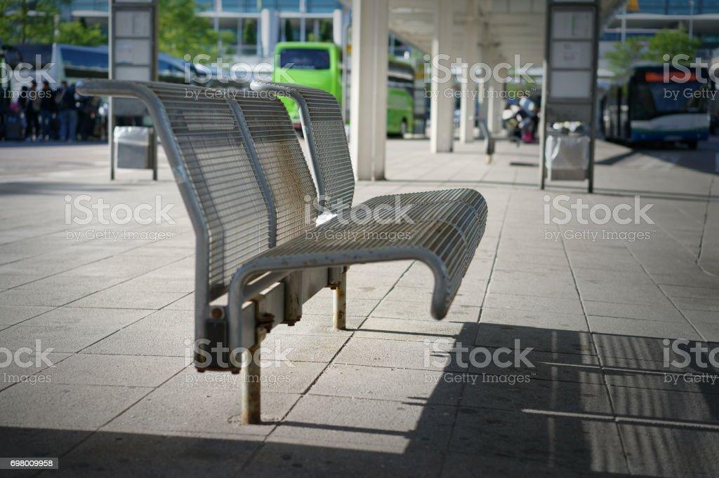The metallic steel mesh bench at the bus terminal stop stock photo