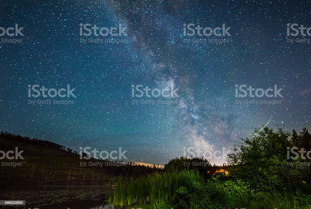 The Milky Way above a forest lake stock photo