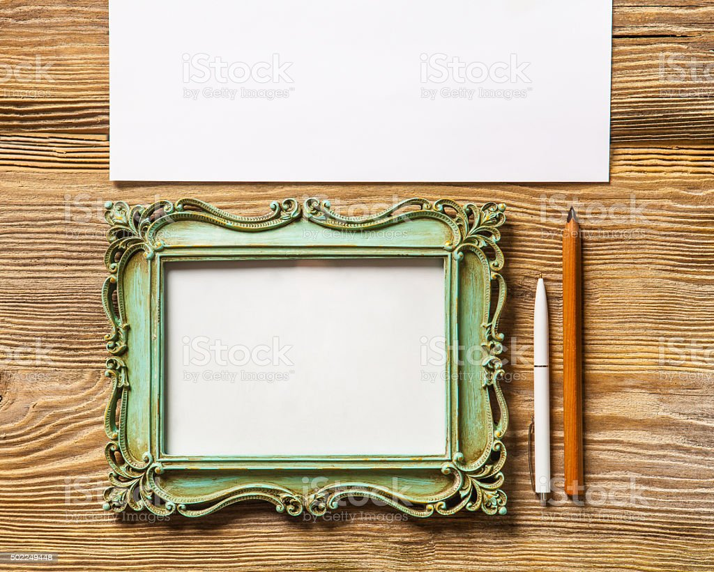 The mockup on wooden background with vintage old picture frame stock photo