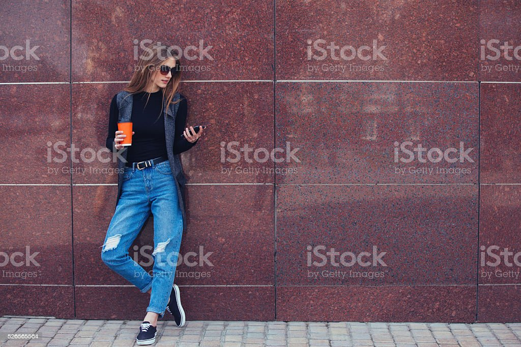 The model stands against the wall and keeps the phone. stock photo