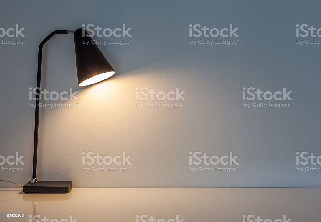 The modern desk lamp illuminate on the wall background. stock photo