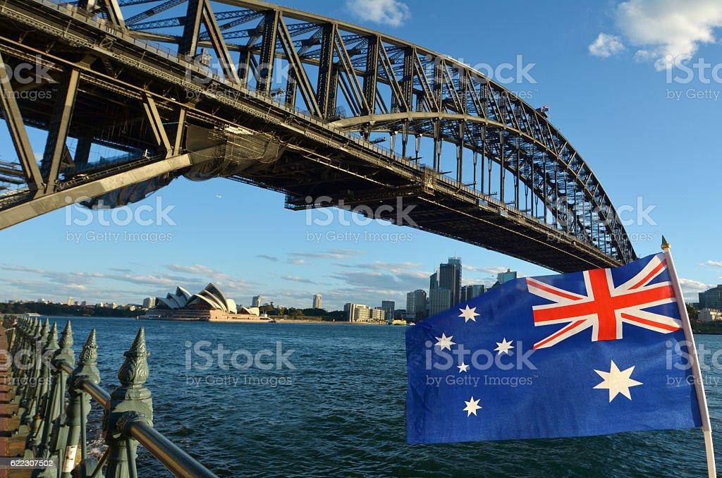The National flag of Australia flies under Sydney Harbour Bridge stock photo