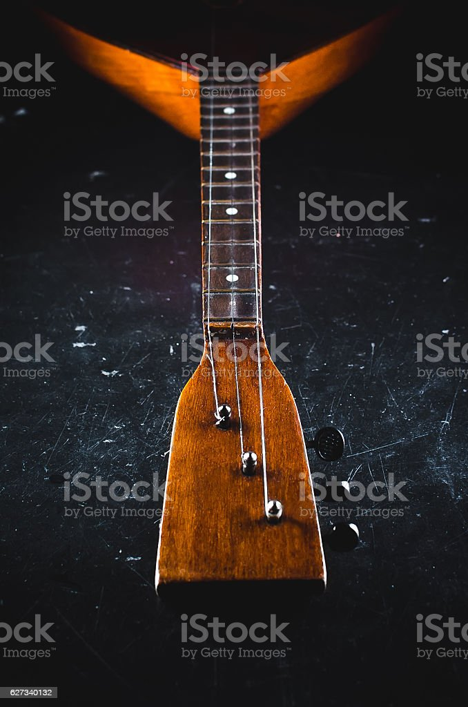 The neck of the guitar on a black stock photo