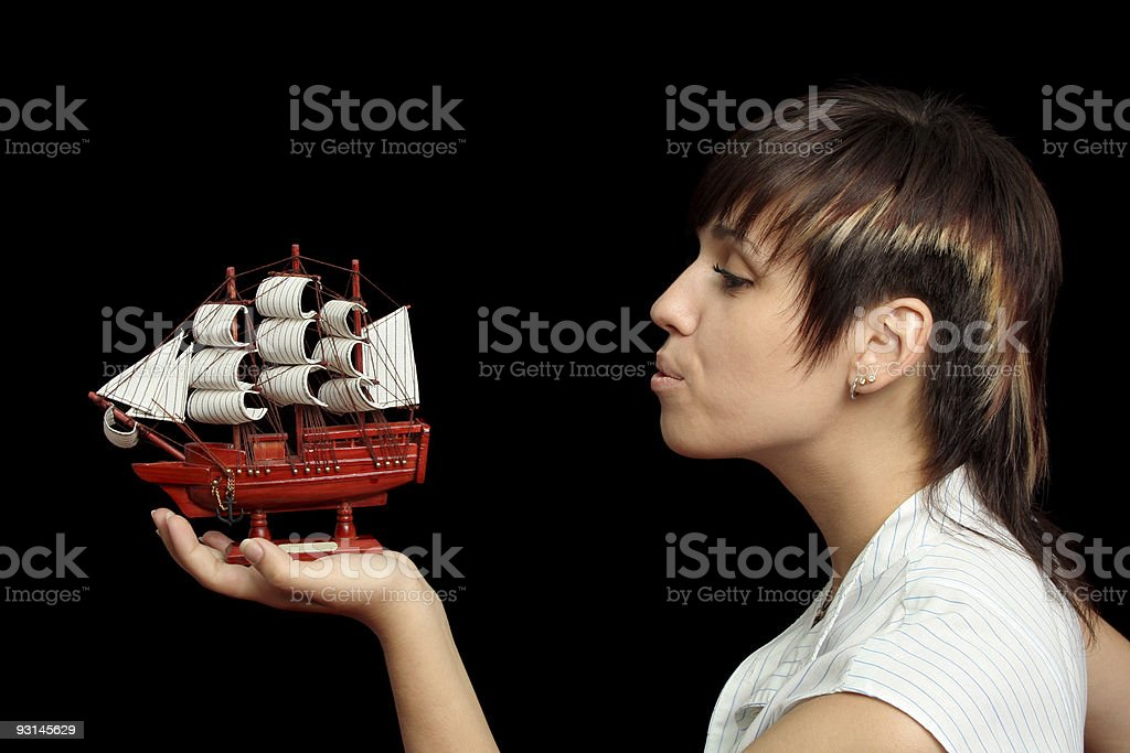 The nice girl blows on a toy ship in hand royalty-free stock photo