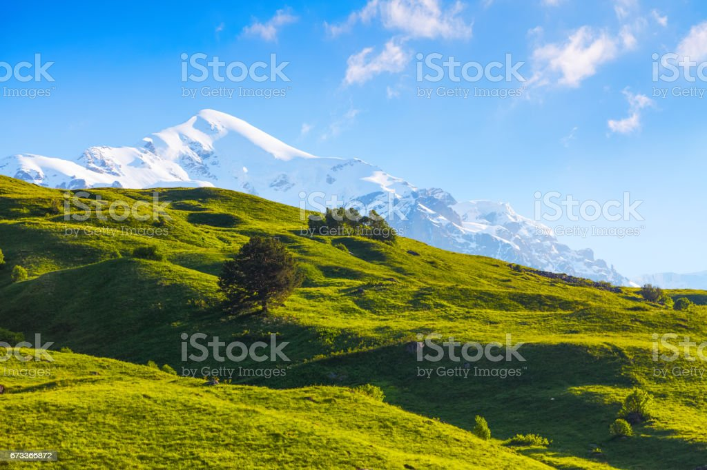 The nice view to the landscape of high mountains in the sunny day is opened from the green valley covered with grass. stock photo