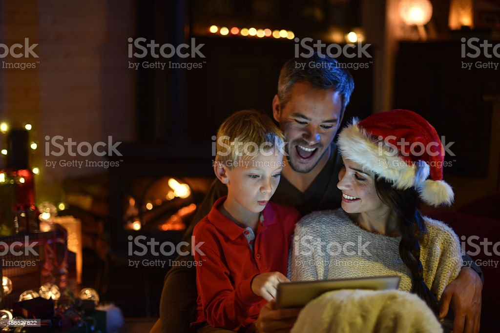 the night christmas, family sharing a digital tablet stock photo