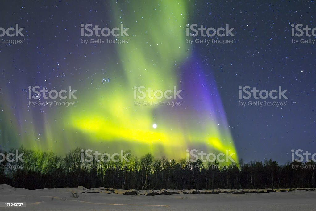 The Northern Lights Aurora borealis over snowy landscape stock photo