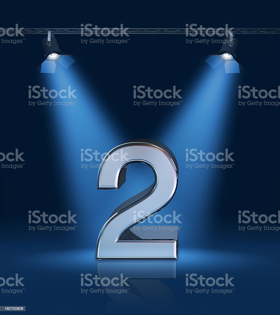 The number 2 depicted on a stage with bright blue lights stock photo