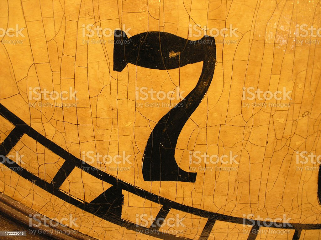The number 7 painted in black on a wooden clock face royalty-free stock photo