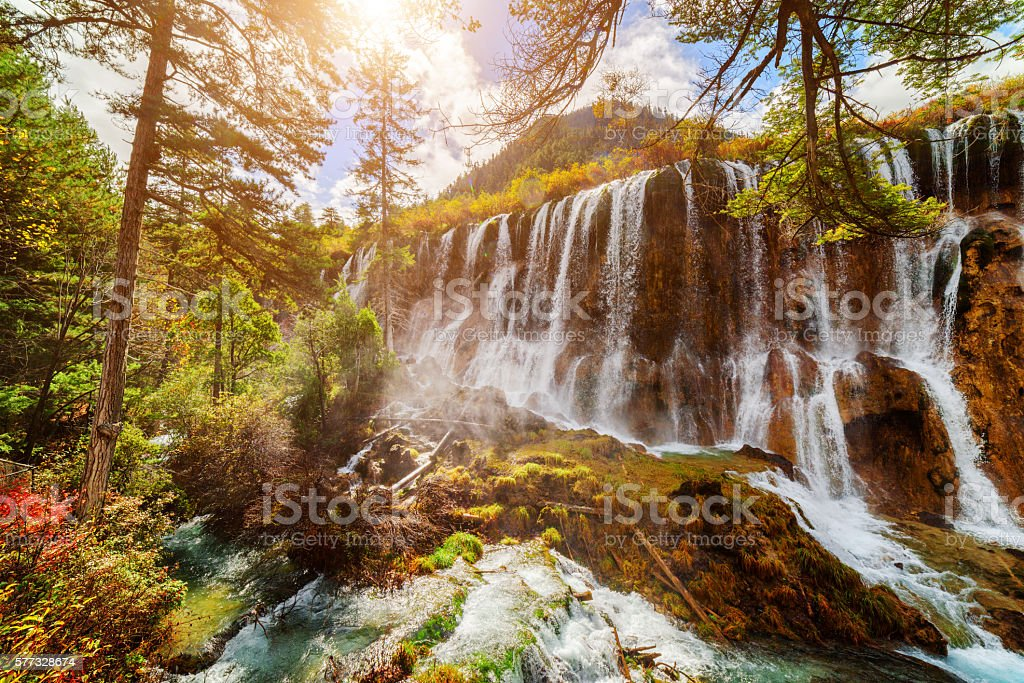 The Nuo Ri Lang Waterfall (Nuorilang) among autumn forest stock photo