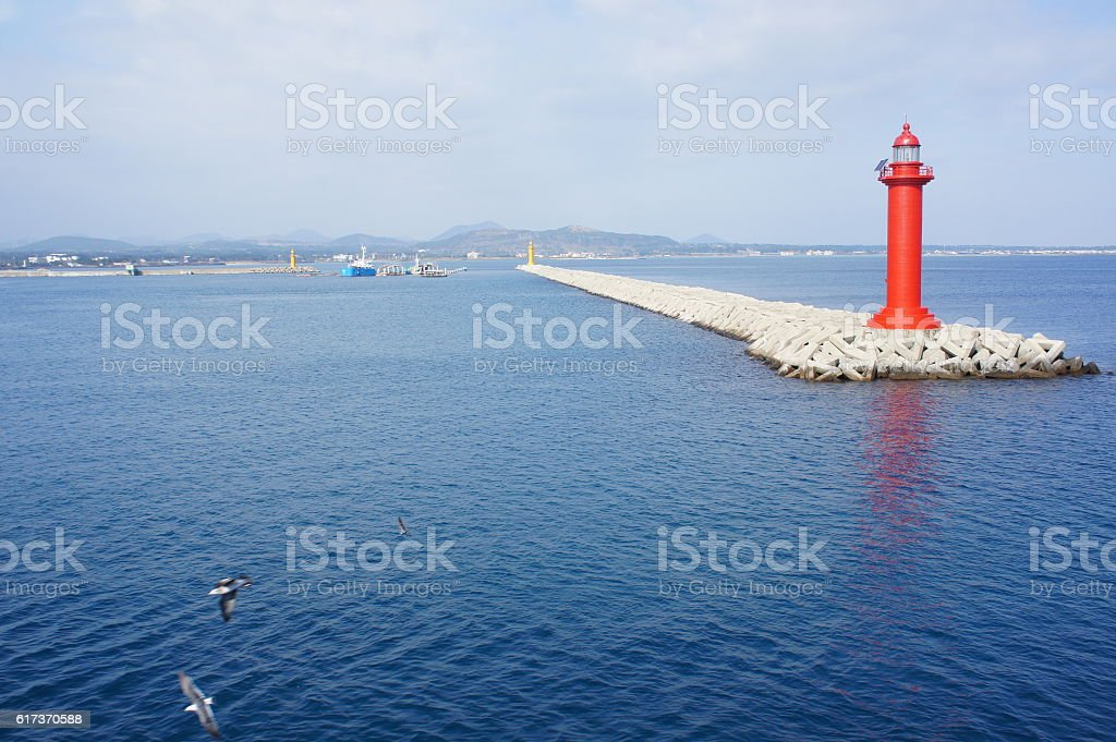 The ocean view with red lighthouse in Jeju island stock photo