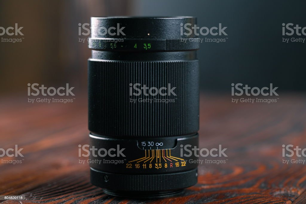 The old 35 mm SLR lens on a wooden background. stock photo