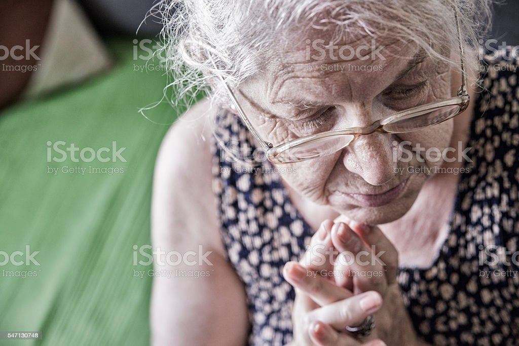 The old and pensive woman prays stock photo