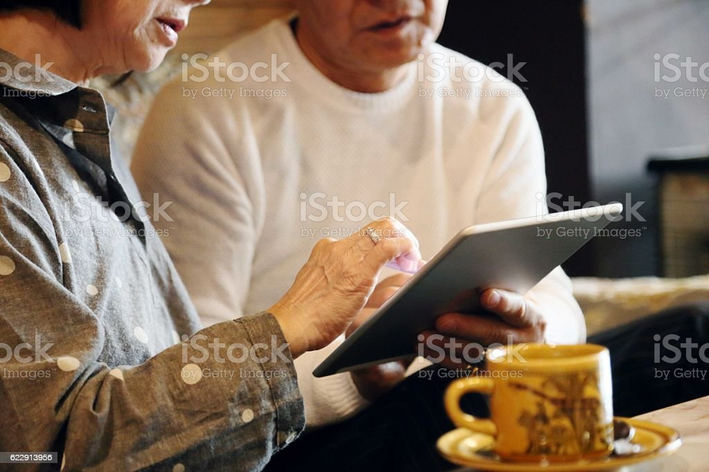 The old couple who performs net shopping with a tablet stock photo