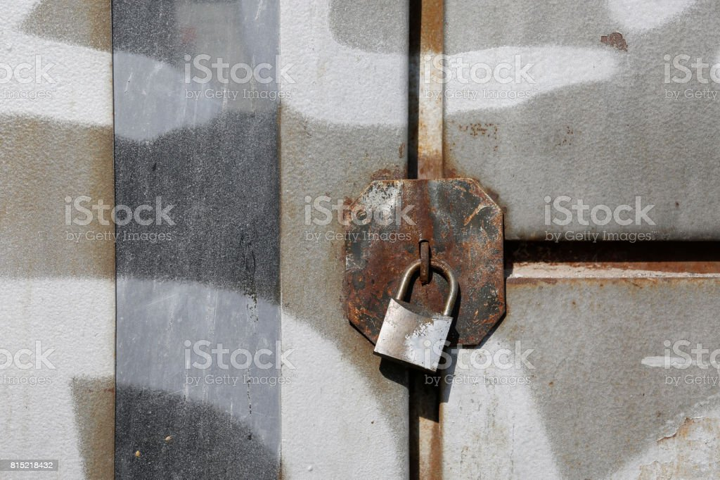 The old door locked with a padlock hanging brackets. stock photo