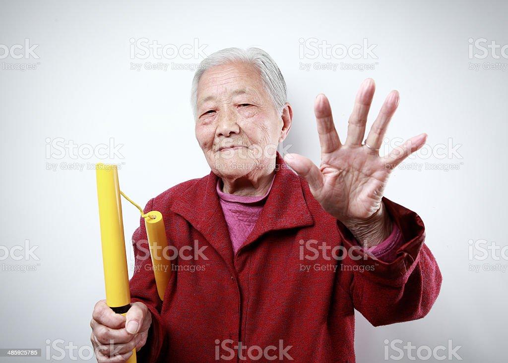 The old granny playing Nunchaku stock photo