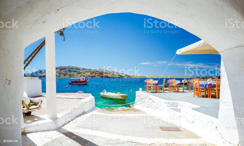 The old harbor of Ammoudi under the famous village of Oia at Santorini, Greece through a frame of an old arched building. stock photo