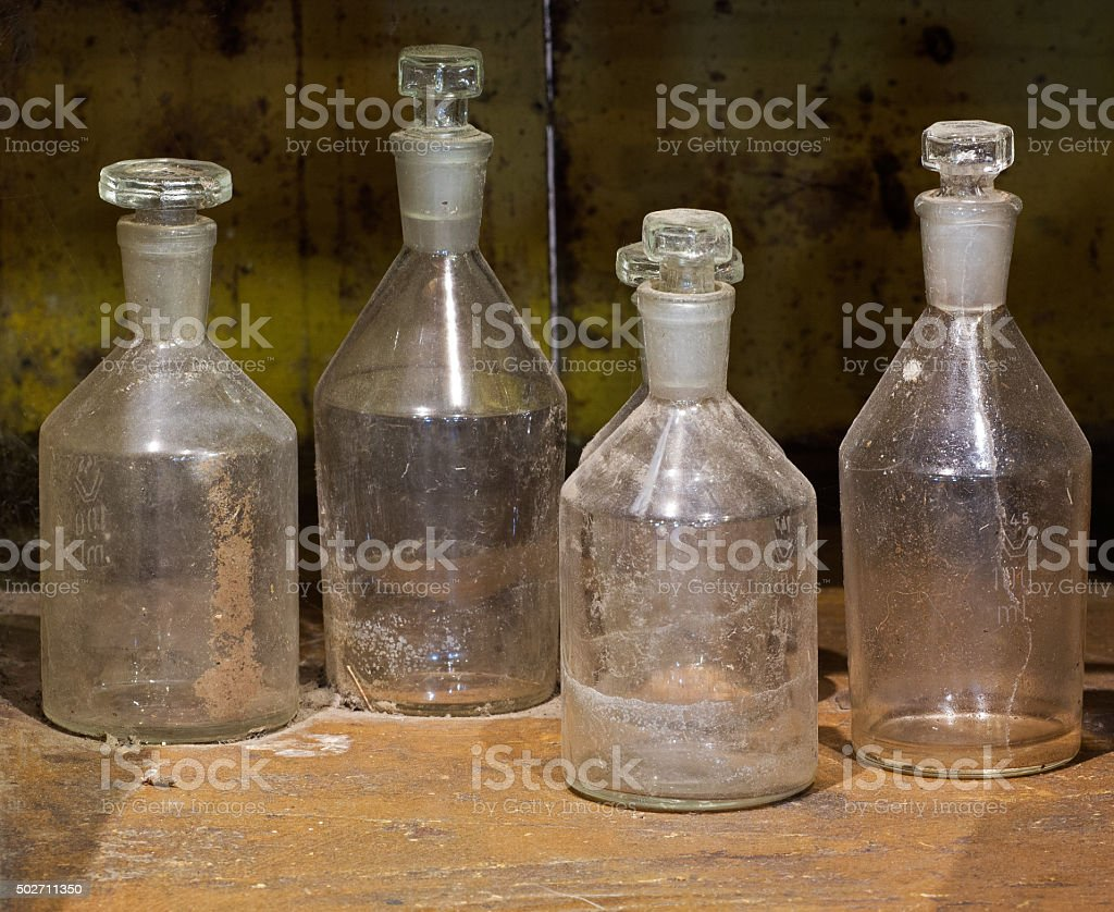 The old Reagent glass bottles on dusty table stock photo