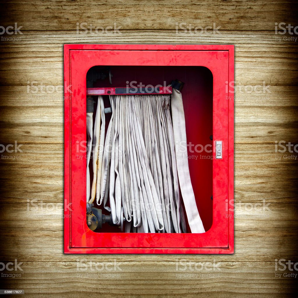 The old red fire hose cabinet on wood background stock photo