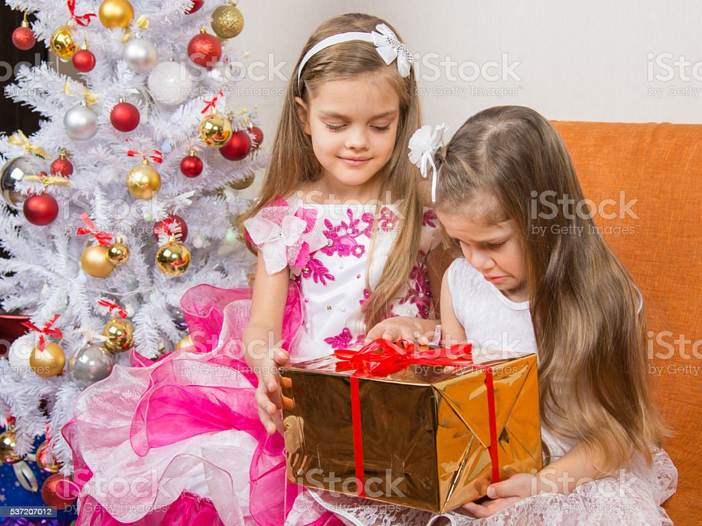 The older girl gives younger unwanted gift stock photo