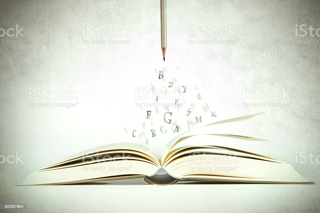 The opened book with alphabet letter flying out of pages stock photo