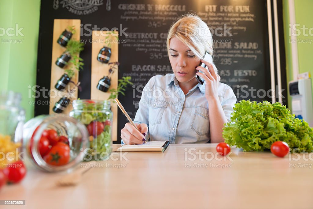 The owner of small restaurant writes order on paper stock photo