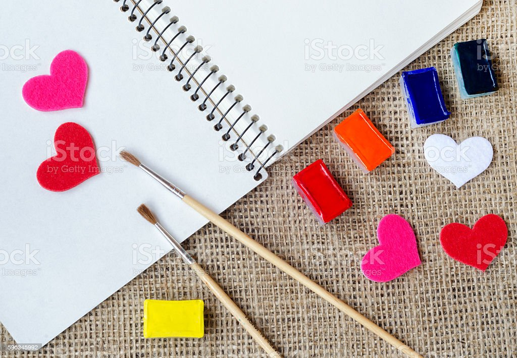 The paper hearts and notebook with brushes on the sackcloth stock photo