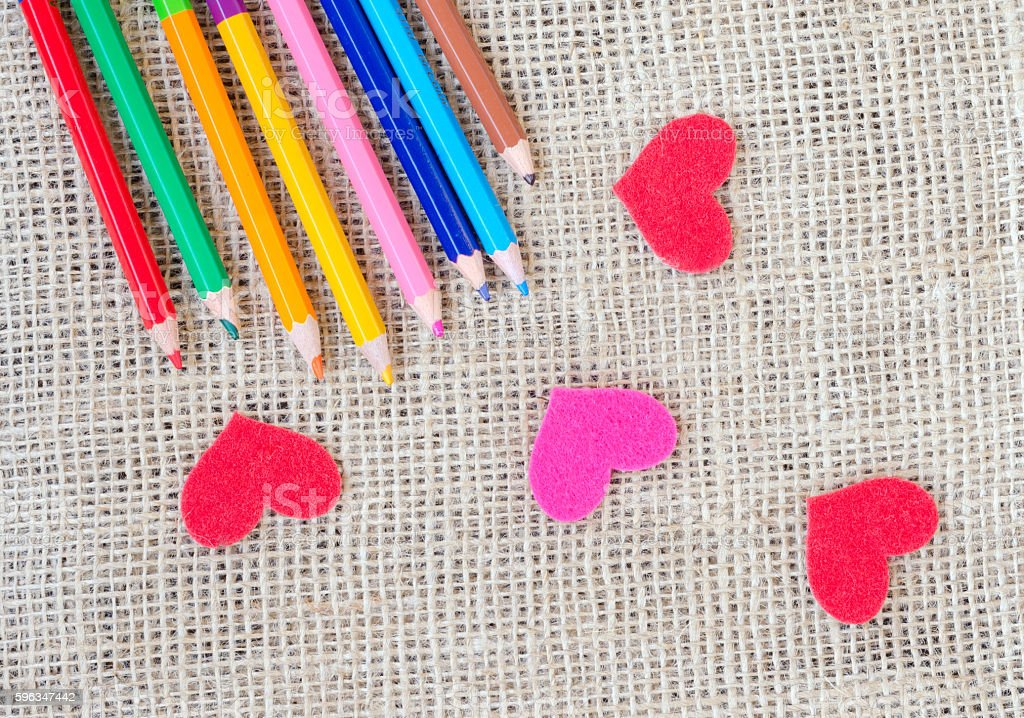 The paper hearts and pencils on the sackcloth stock photo