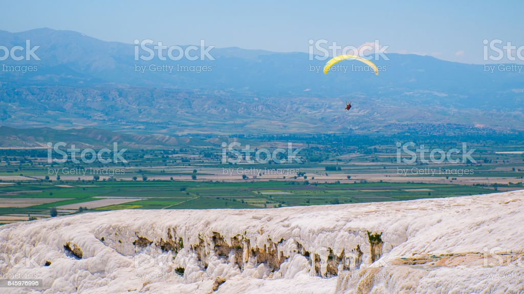 The paratrooper flies over amazing hot springs and huge white terraces of travertine, left by the flowing water. stock photo