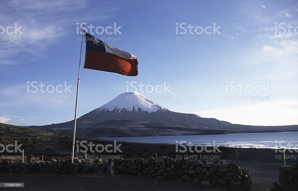 The Parinacota volcano with chilean flag stock photo