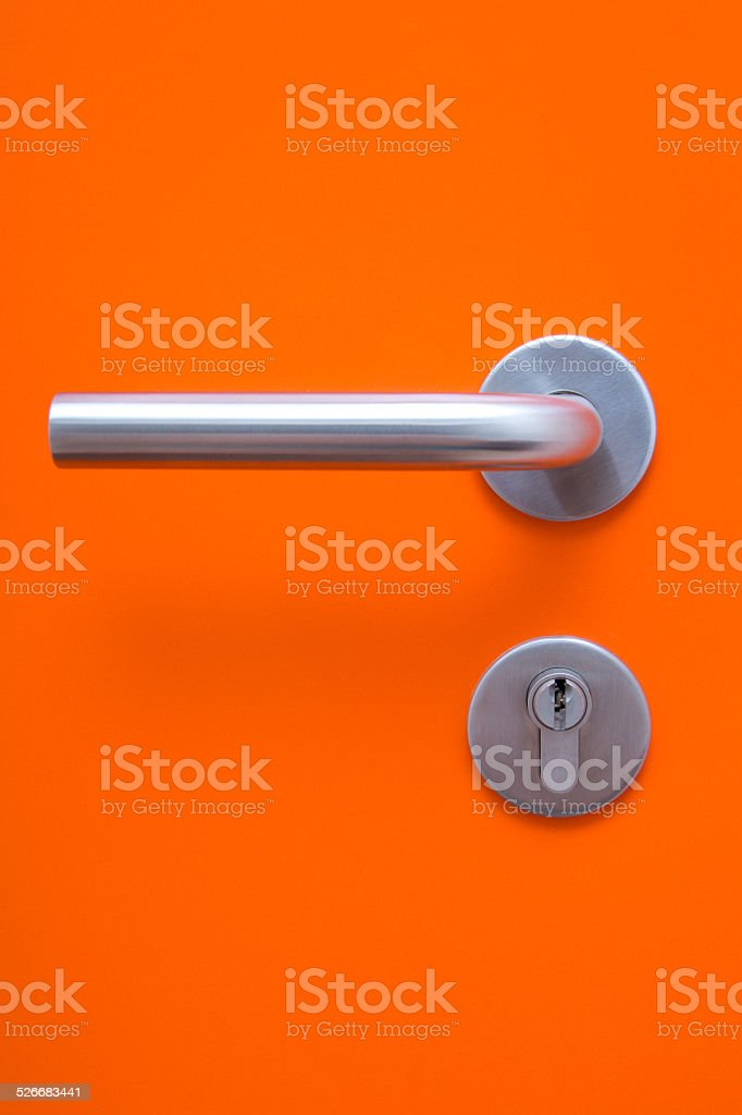 the part of orange door with metal handle stock photo