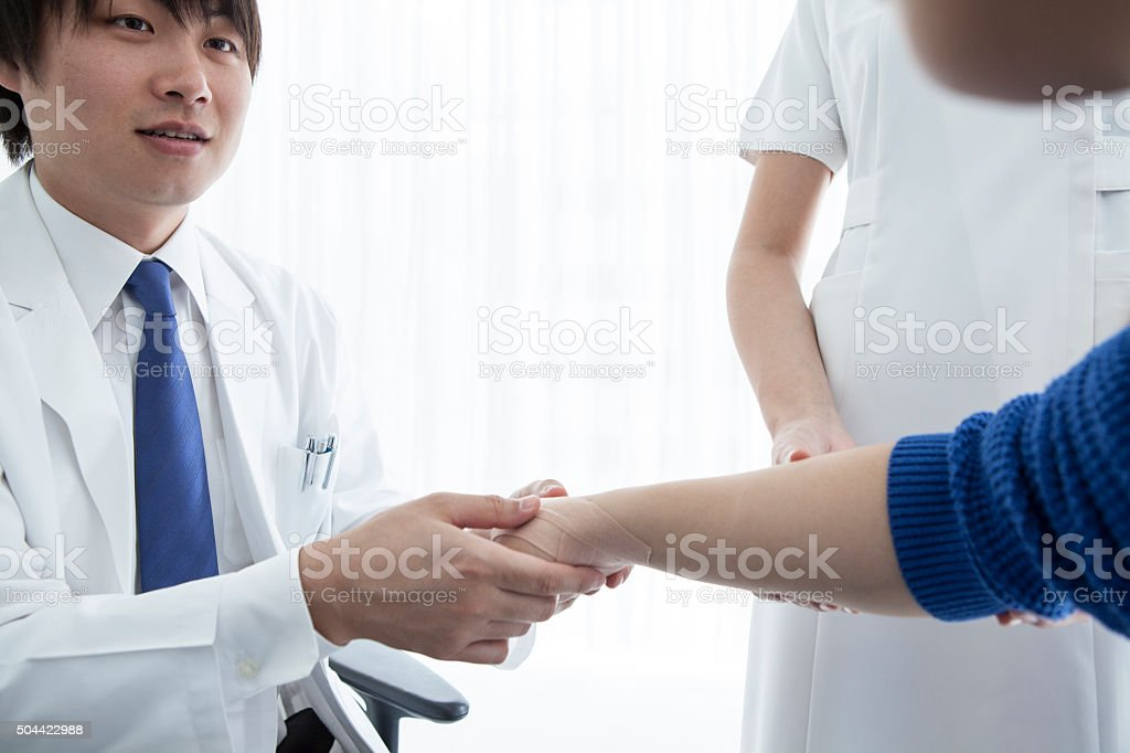 The patient has been taping the hand to the doctor stock photo