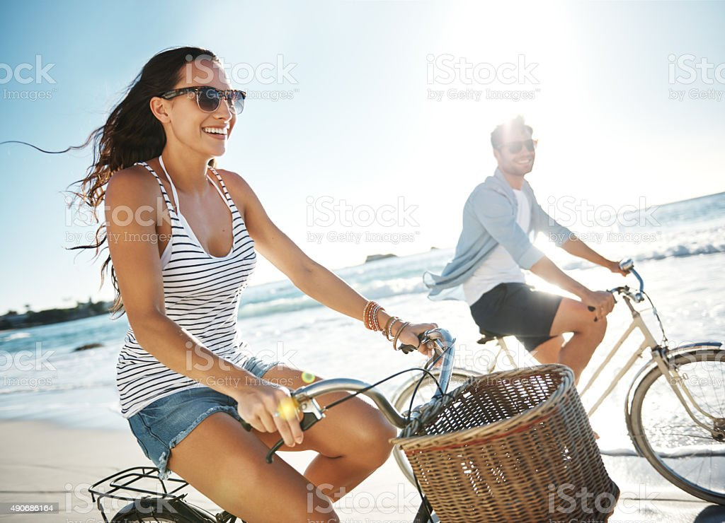 Cropped shot of a young couple cycling on the...