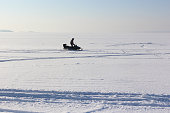 The person going on a snowmobile on the frozen river
