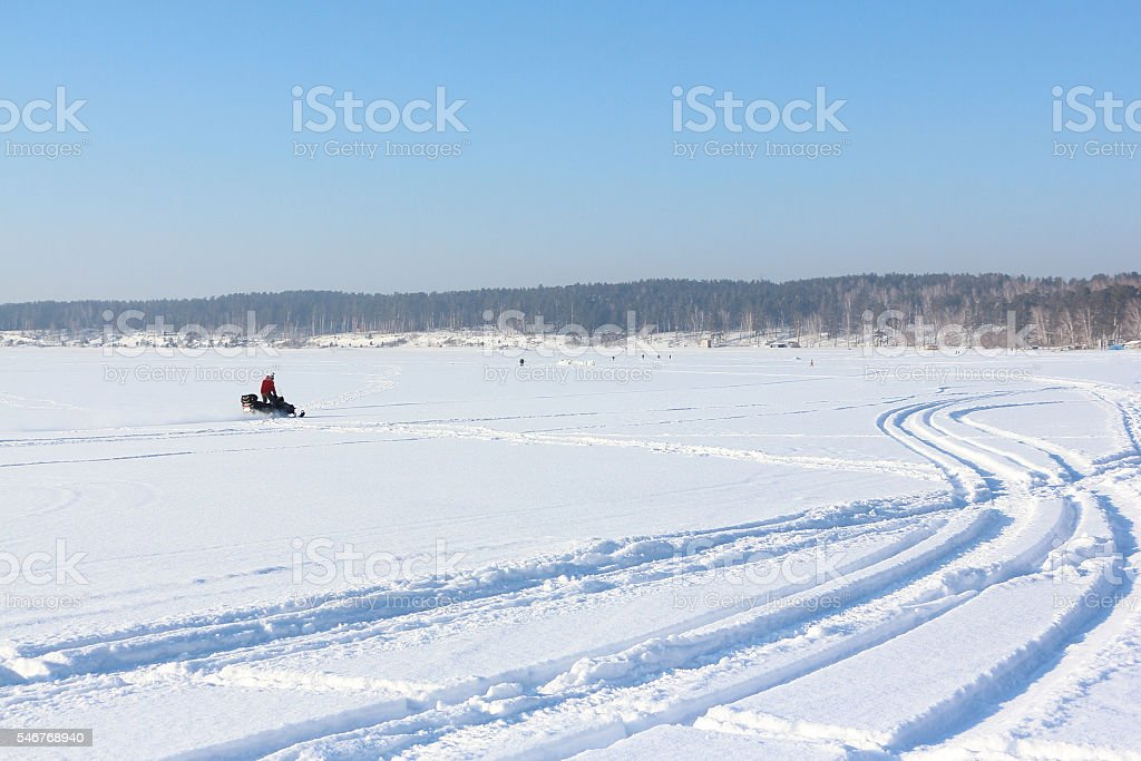 The person going on a snowmobile on the frozen river stock photo