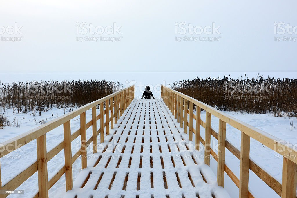 The person sits on the embankment in the winter stock photo