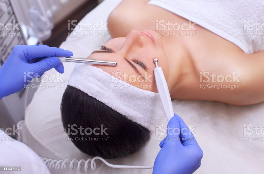 The physician-cosmetologist makes Electric Facial Treatment of the skin of a beautiful, young woman in a beauty salon. stock photo