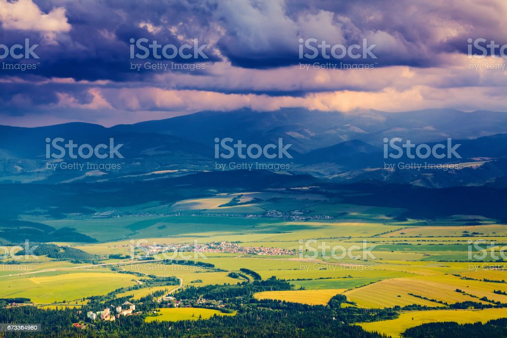 The picture captures the view of a  person watching meadow reverie,  fantastic mountains and the clouds floating across the sky. stock photo