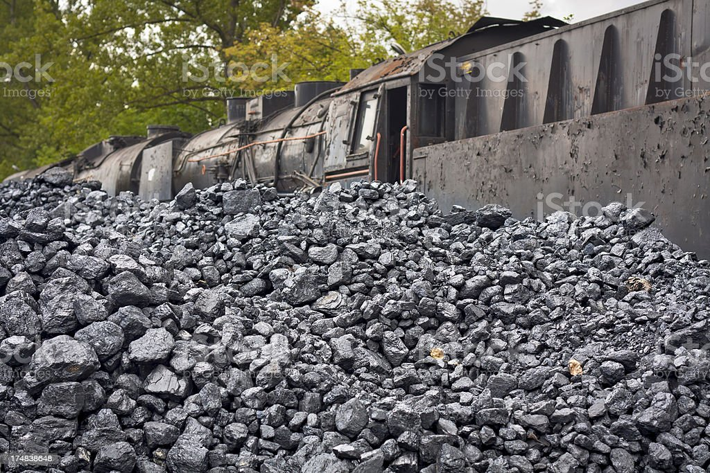 The pile of coal and rusty steam locomotive royalty-free stock photo