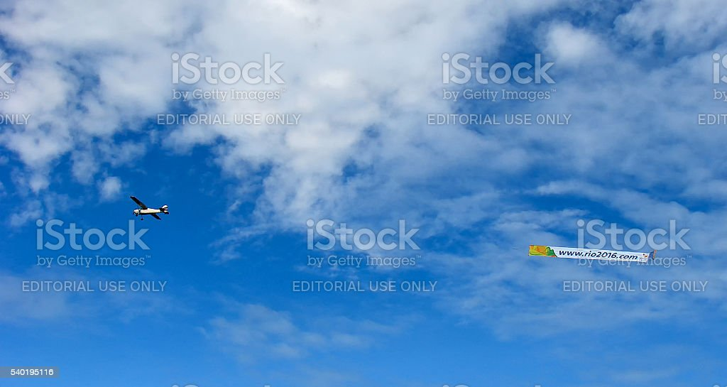 The plane with developing a banner in the blue cloudy sky stock photo