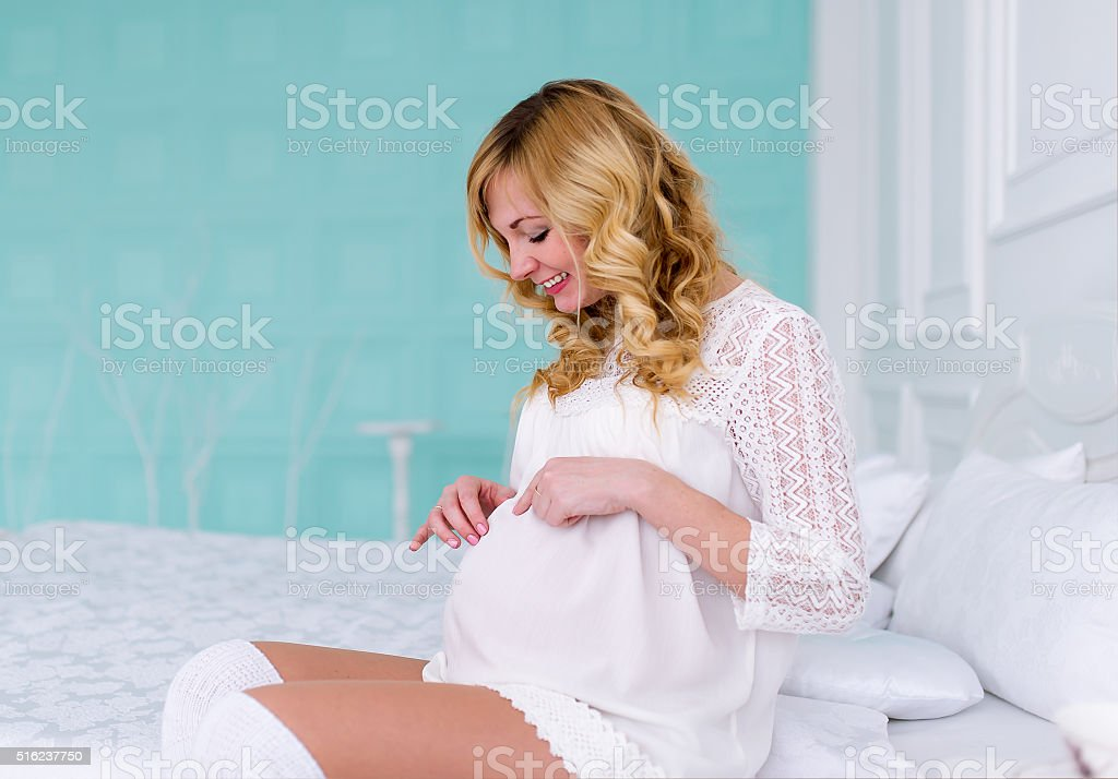 The pregnant woman sits in the bedroom on bed. stock photo