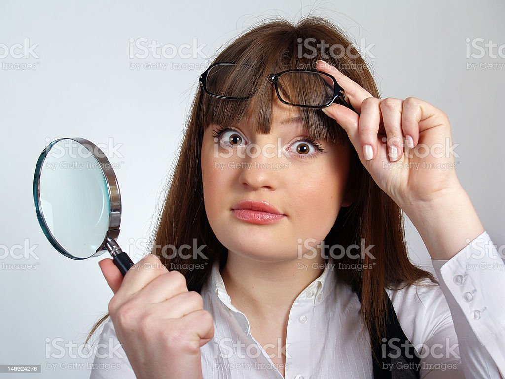 The pretty young woman with a magnifier in her hand royalty-free stock photo