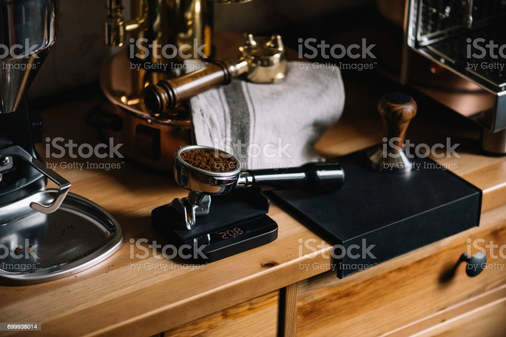 The process of making coffee step by step. Delicious morning freshly ground coffee inside a portafilter on wooden table stock photo