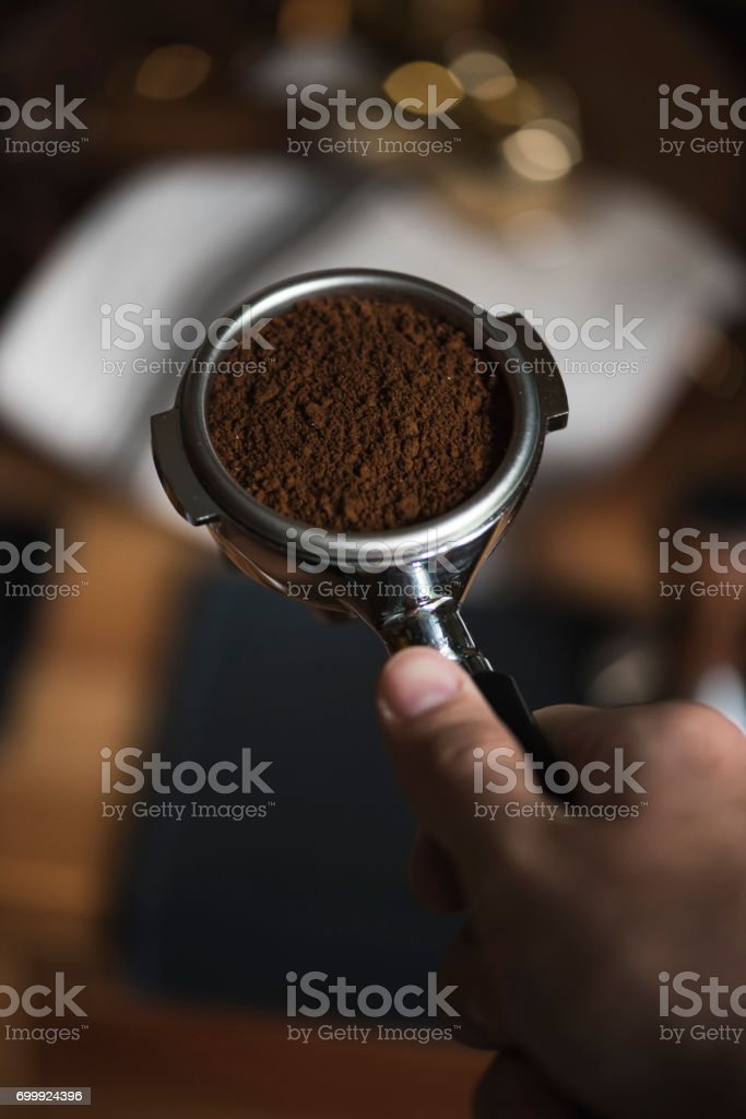 The process of making coffee step by step. Man is performing coffee grooming before tamping to flatten the surface of the ground coffee. stock photo