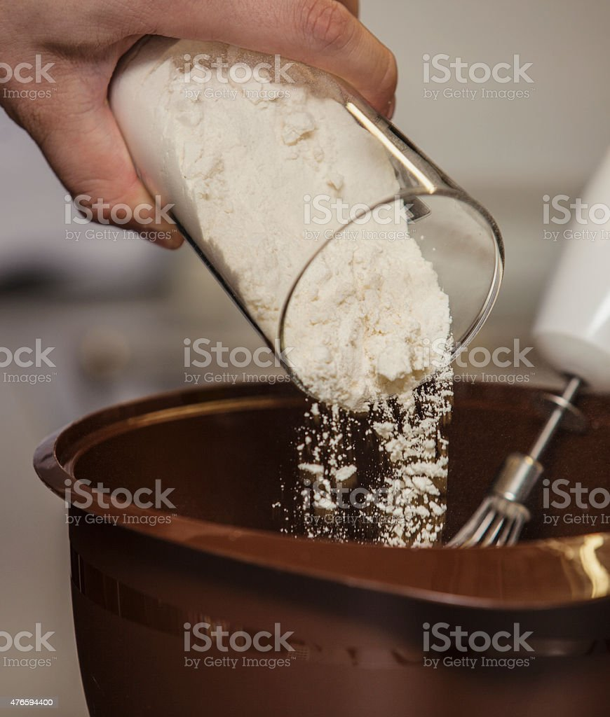 The process of preparing dough in a Cup stock photo