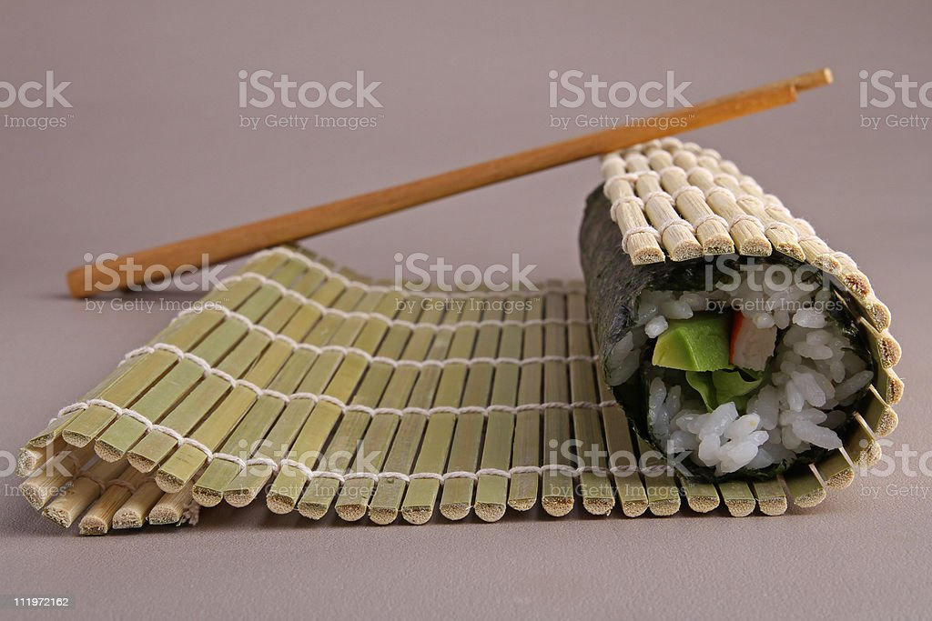 The process of sushi making - bamboo roller and seaweed royalty-free stock photo