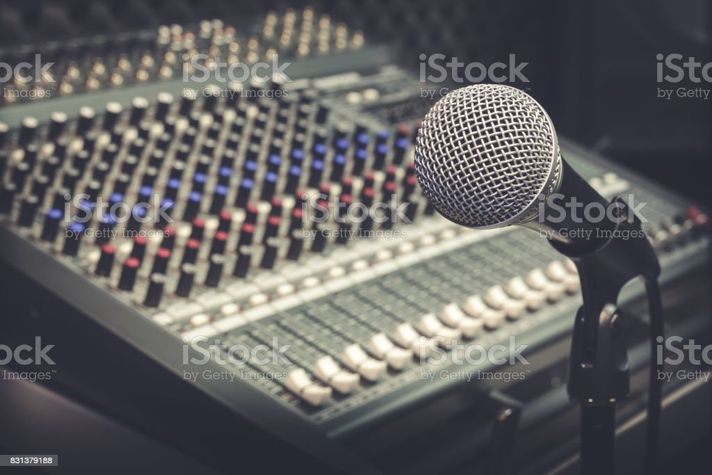 The producer music or musician equipment concept.Selective focus of single microphone with sound music mixer at the recording studio room.Vintage tone design background. stock photo