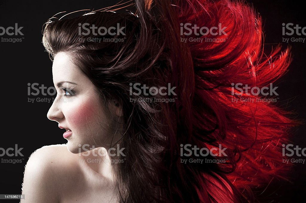 The profile of a brunette and her hair with red tips stock photo