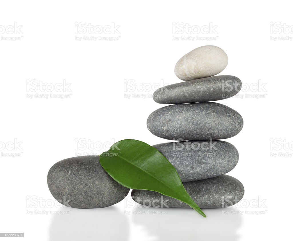 The pyramid of round stones with green leaf royalty-free stock photo
